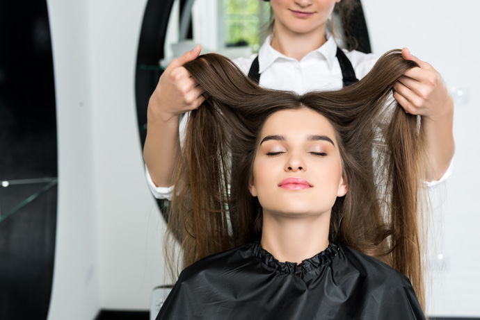 happy young woman with beautiful hair in hair salon